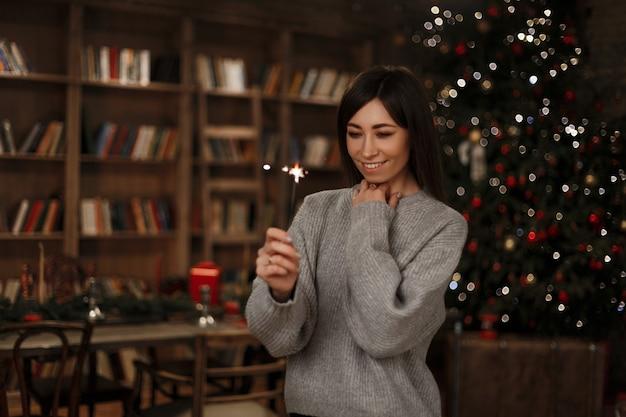 La giovane donna in un maglione caldo lavorato a maglia tiene una stella filante in sua mano sorride e la guarda vicino a una libreria vintage in una stanza festiva. ragazza allegra. Foto Premium