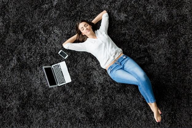 Giovane donna che pone sul tappeto Foto Premium