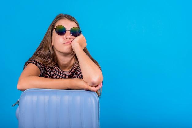 Giovane donna che si appoggia sulla valigia blu Foto Premium