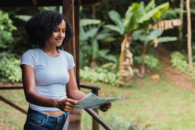 Giovane donna che guarda una mappa Foto Premium