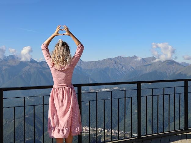 Giovane donna che guarda le montagne e che fa il segno del cuore con le mani Foto Premium