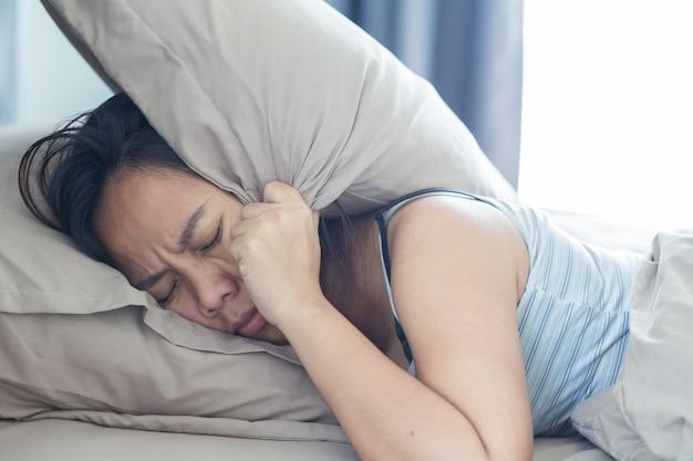 Giovane donna sdraiata a letto che soffre di suono che copre la testa e le orecchie con il cuscino Foto Premium