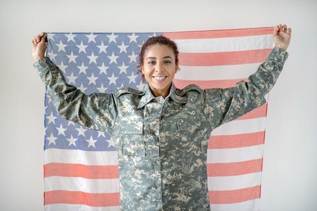 Giovane donna in uniforme militare che tiene la bandiera americana Foto Premium