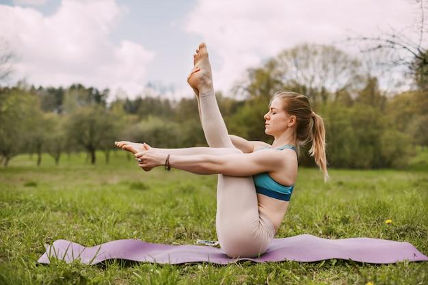 Una giovane donna esegue asana yoga all'aperto in un parco. Foto Premium