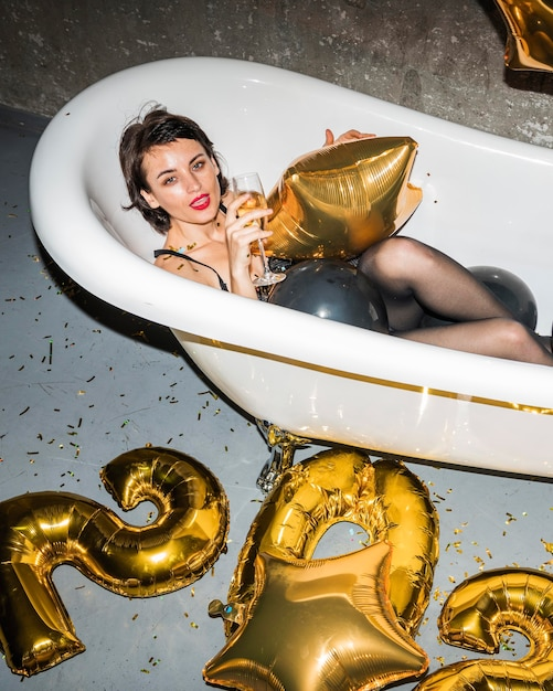 Giovane donna in posa nella vasca da bagno a casa Foto Premium