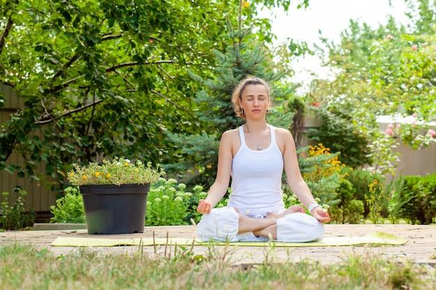 Giovane donna pratica yoga in giardino Foto Premium