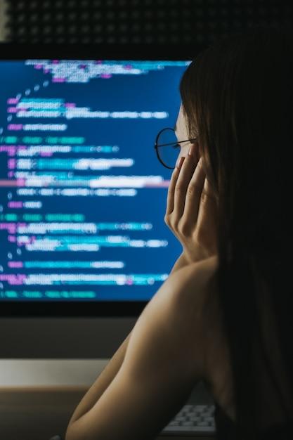 Il programmatore della giovane donna scrive il codice del programma sul computer Foto Premium