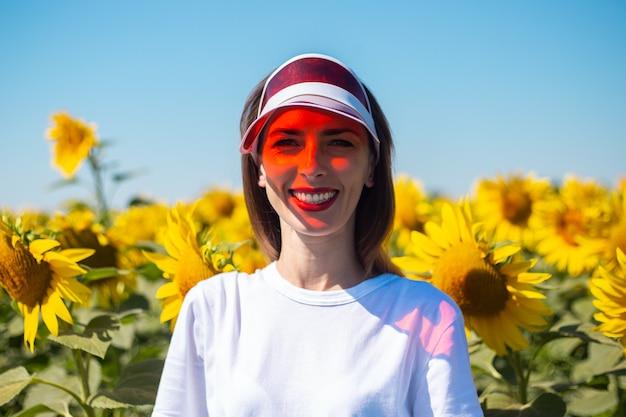 Giovane donna in visiera parasole rossa e maglietta bianca sul campo di girasoli. Foto Premium
