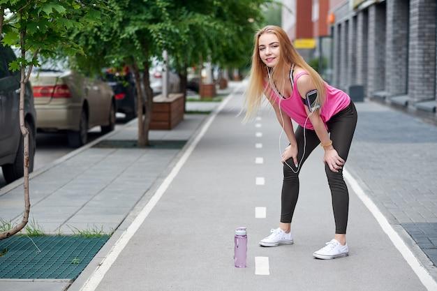 Giovane donna che riposa dopo aver corso su un vicolo della città con una bottiglia di acqua Foto Premium