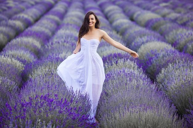 Giovane donna che funziona nel campo di lavanda. bella donna su sfondo floreale estivo Foto Premium