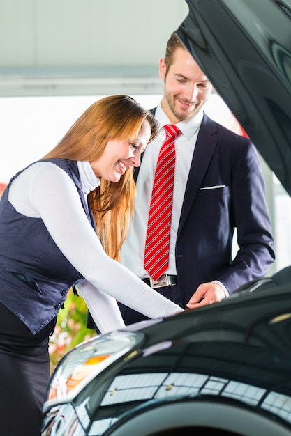 Giovane donna e venditore con auto nel concessionario auto Foto Premium