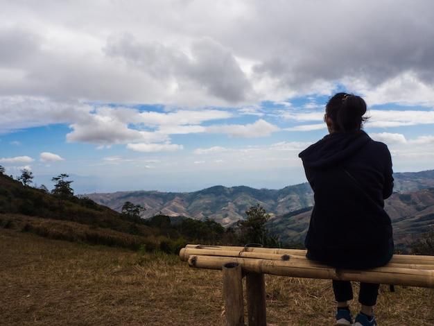 La giovane donna che si siede sulla sedia e vede il cielo, sieda da solo Foto Premium