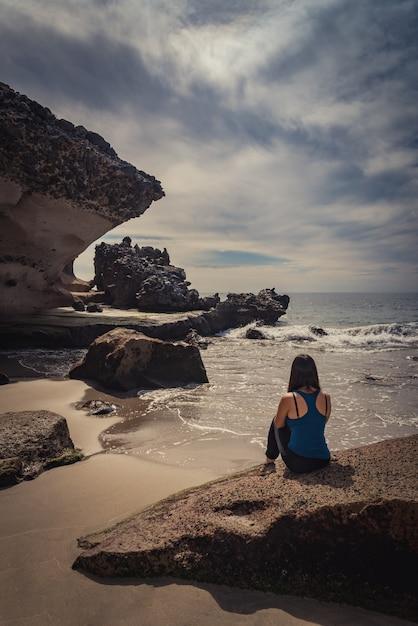 Giovane donna seduta su una pietra sulla spiaggia che guarda al mare Foto Premium