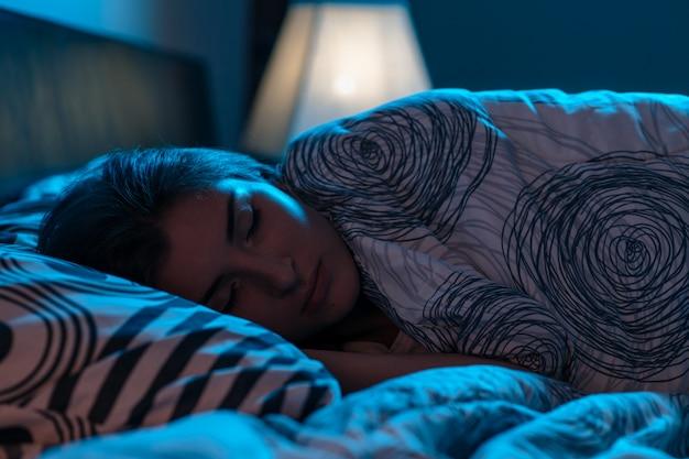 Giovane donna che dorme in un letto in una camera da letto buia Foto Premium
