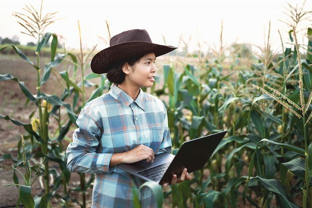 Computer portatile di uso diritto della giovane donna che controlla cereale in azienda agricola. tecnologia agricoltura conept Foto Premium