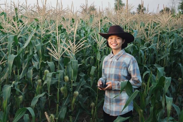 Cereale di controllo mobile di uso diritto della giovane donna in azienda agricola. tecnologia agricoltura conept Foto Premium