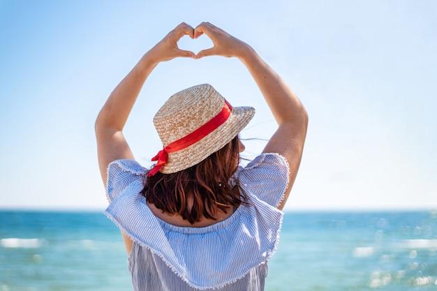 La giovane donna in un cappello di paglia e una vista delle spalle del vestito da estate fa il segno di amore con le sue mani sul mare blu Foto Premium