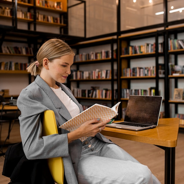 Giovane donna che studia in biblioteca Foto Premium