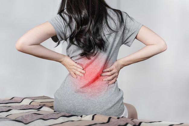 Giovane donna che soffre di mal di schiena sul letto dopo il risveglio Foto Premium