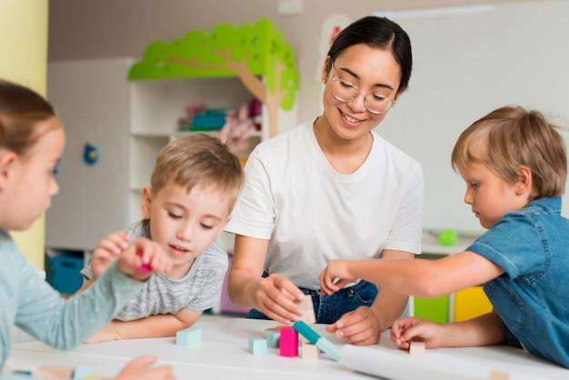 Giovane donna che insegna ai bambini come giocare con il gioco colorato Foto Premium