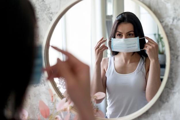 Giovane donna che prova la mascherina medica Foto Premium