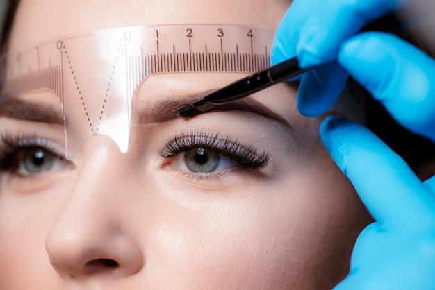 Giovane donna che subisce la procedura di correzione del sopracciglio su sfondo chiaro Foto Premium