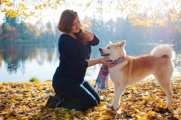 Giovane donna in una passeggiata con il suo cane akita inu di razza Foto Premium