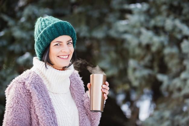 Giovane donna che cammina il giorno di inverno, tenendo tazza da viaggio in acciaio inossidabile con caffè caldo. bottiglia d'acqua riutilizzabile. Foto Premium