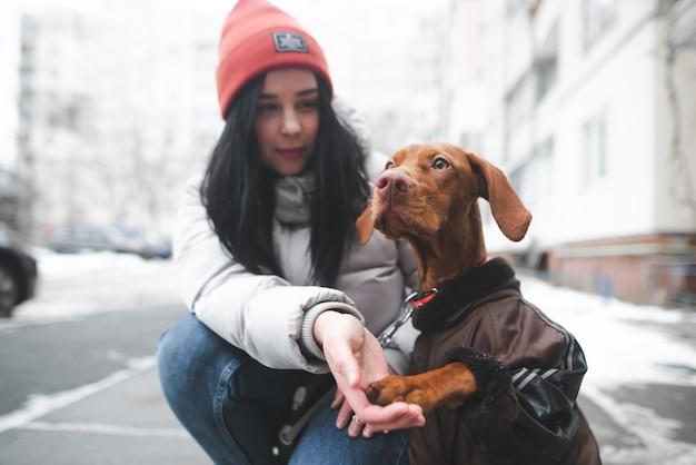 Giovane donna in abiti caldi si siede a terra con un cucciolo Foto Premium