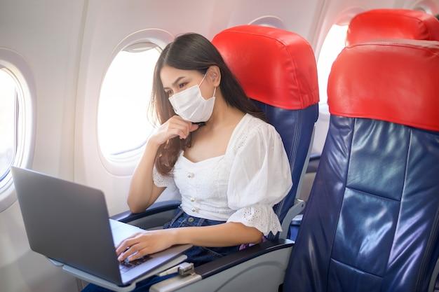 Una giovane donna che indossa una maschera per il viso sta usando il laptop a bordo, nuovo viaggio normale dopo il concetto di pandemia covid-19 Foto Premium