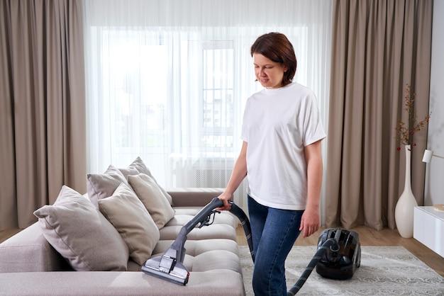 Giovane donna in camicia bianca e jeans pulizia tappeto sotto il divano con aspirapolvere in soggiorno, copia dello spazio. concetto di lavori domestici, pulizie e faccende Foto Premium