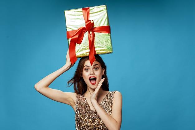 Giovane donna con scatole di regali nelle sue mani in studio su una superficie colorata in bellissimi abiti, vendita di regali, buon natale e capodanno Foto Premium
