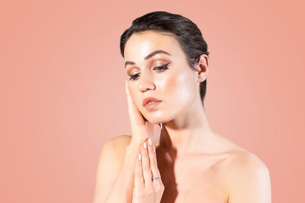 Giovane donna con la pelle chiara che tocca le sue mani il suo viso. Foto Premium