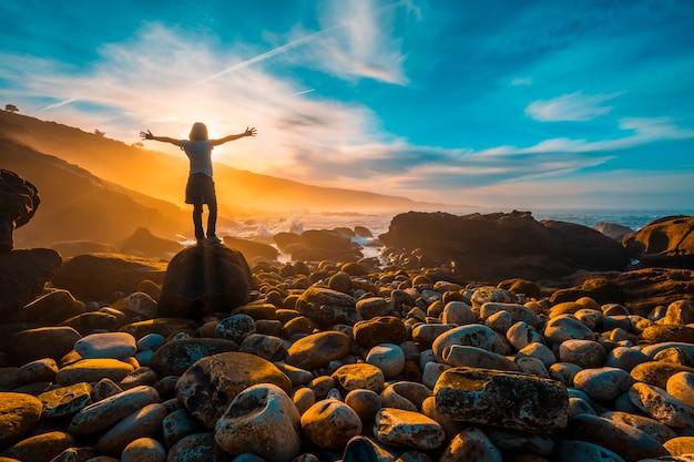 Una giovane donna con le braccia spalancate al tramonto sulla costa di jaizkibel vicino a san sebastian. paesi baschi Foto Premium