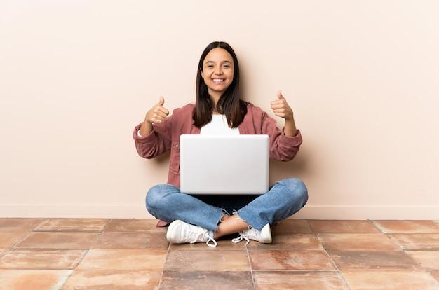 Giovane donna con un computer portatile seduto sul pavimento dando un pollice in alto gesto Foto Premium