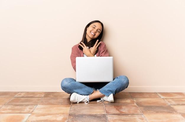 Giovane donna con un laptop seduto sul pavimento sorridendo e mostrando il segno di vittoria Foto Premium
