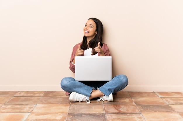 Giovane donna con un computer portatile che si siede sul pavimento sorpreso e che indica davanti Foto Premium