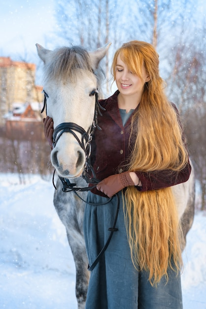 Giovane donna con i capelli lunghi con cavallo in inverno ...