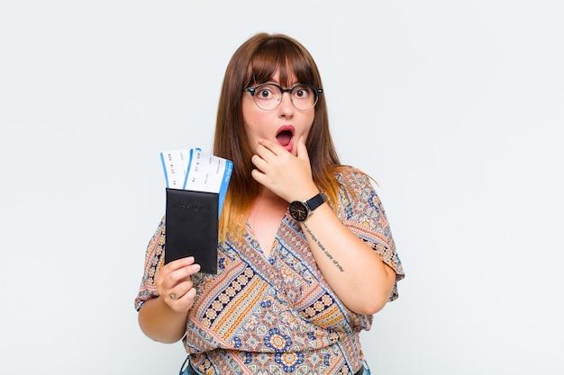 Giovane donna con la bocca e gli occhi spalancati e la mano sul mento, che si sente spiacevolmente scioccata, dice cosa o wow Foto Premium