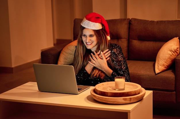 Giovane donna con il cappello di babbo natale che fa una videochiamata alla sua famiglia per festeggiare il natale. concetto di solitudine, famiglia separata, distanza sociale e natale. Foto Premium