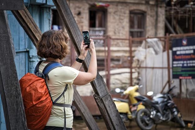 Giovane donna con i capelli corti bruna fotografare con il suo smartphone un tempio indù in nepal, asia. zaino arancione con rivestimento impermeabile Foto Premium