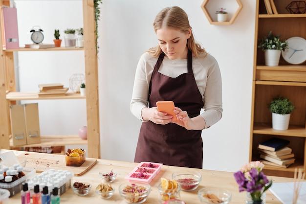 Giovane donna con lo smartphone che cattura foto di sapone fatto a mano in stampi in silicone sul tavolo di legno in studio Foto Premium