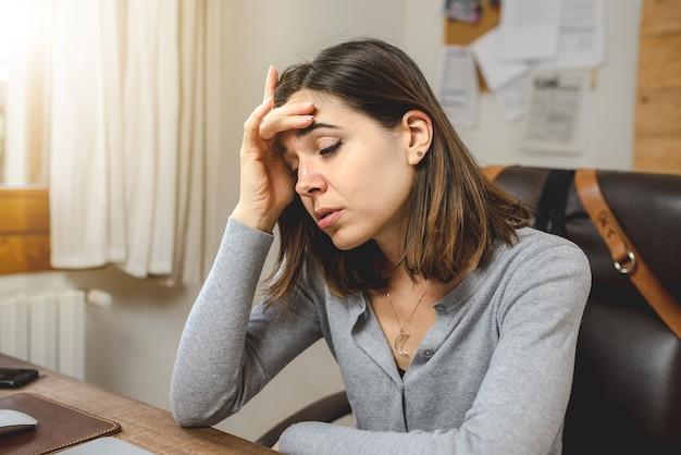 Giovane donna che lavora o studia alla scrivania stanco e stressato mette la mano sulla testa. Foto Premium