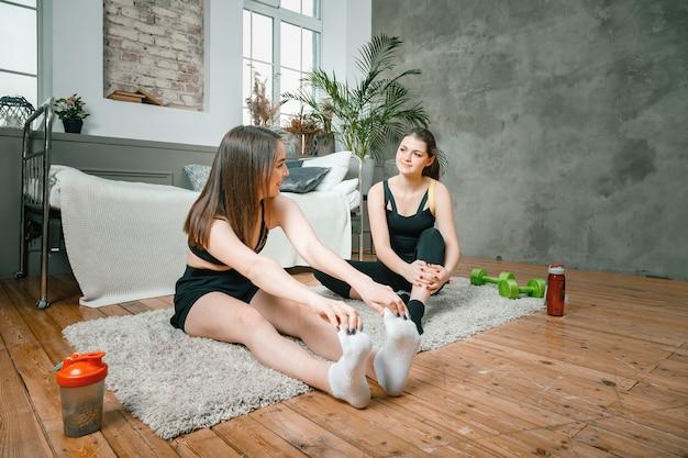 Le giovani donne praticano sport a casa, si allenano online Foto Premium