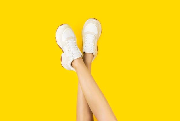 Giovani donne in eleganti scarpe da ginnastica su uno sfondo giallo. Foto Premium