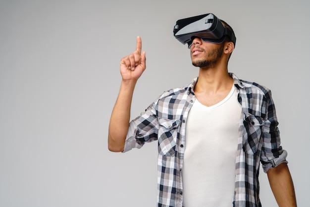 Giovane giovane che indossa le cuffie da realtà virtuale vr sul muro grigio chiaro Foto Premium