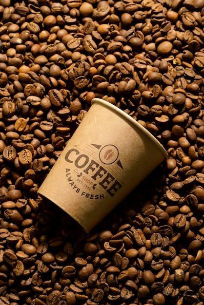 Chicchi di caffè aromatici e tazza di carta mockup. Psd Premium