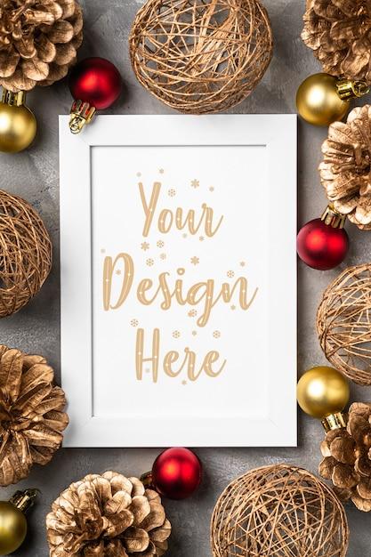 Composizione di natale con cornice vuota ornamento dorato pigne decorazioni mock up modello di biglietto di auguri Psd Premium