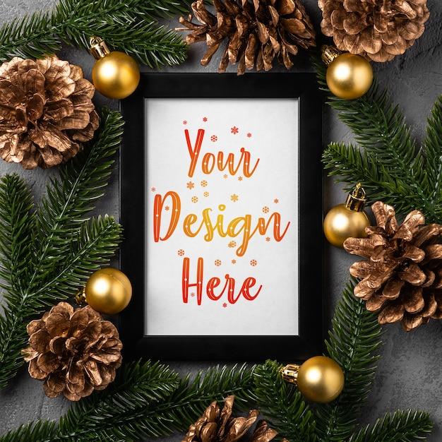 Composizione in natale con cornice vuota. ornamenti dorati, pigne e aghi di abete. mock up modello di biglietto di auguri Psd Premium