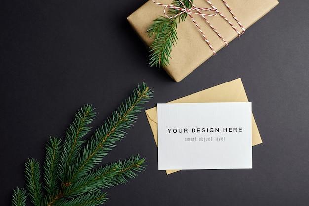 Mockup di biglietto di auguri di natale con scatola regalo e rami di abete sul nero Psd Premium